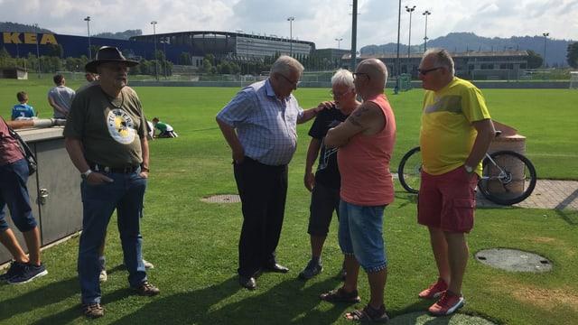 Vier ältere Herren stehen am Rend des Spielfelds, diskutieren, klopfen sich auf die Schulter