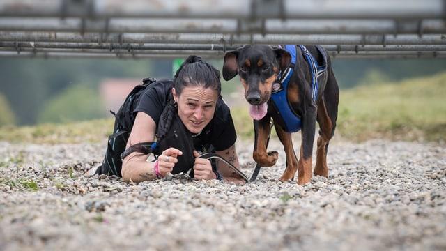 Eine Frau kriecht mit ihrem Hund unter Stangen durch ein Kiesbett.