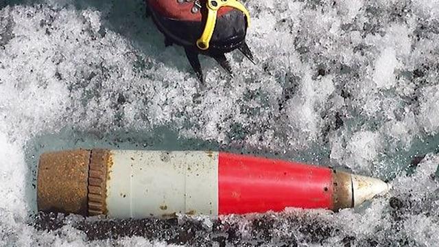 Eine Beleuchtungsgeschoss-Blindgänger im Schnee, darüber ein Wanderschuh mit Spikes.