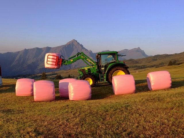 Ein Traktor in einer Berglandschaft hebt rosa Heuballen an.