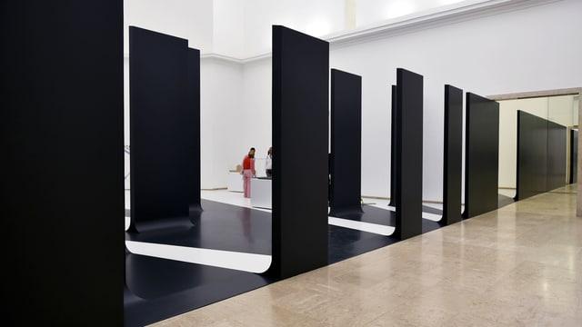 Schwarze Elemente einer Mauer mit Lücken dazwischen