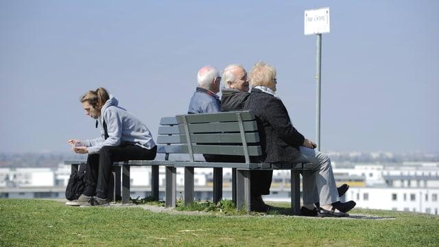 Symbolbild: Auf einer Bank sitzen Rücken an Rücken einige ältere und eine junge Person.