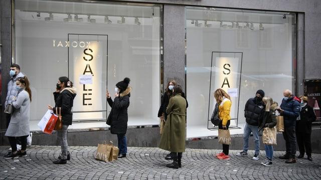 Menschen stehen vor einem Laden Schlange