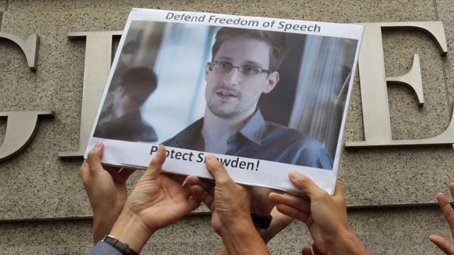 Hände halten ein Bild von Snowden mit der Aufsschrift «Defend Freedom of Speach. Protect Snowden!» in die Höhe.