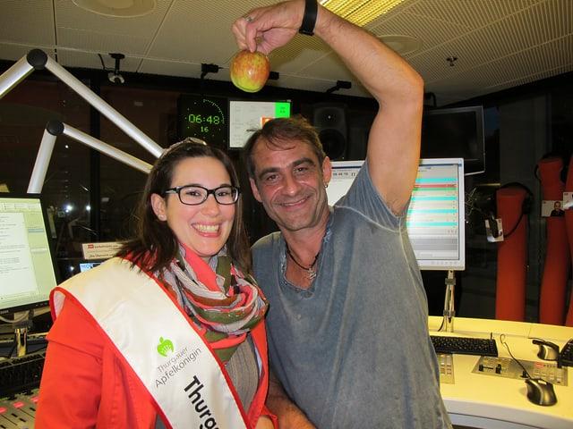 Stefanie König und Thomy Scherrer stehen nebeneinander im Radiostudio, Thomy Scherrer hält einen Apfel in der Hand.