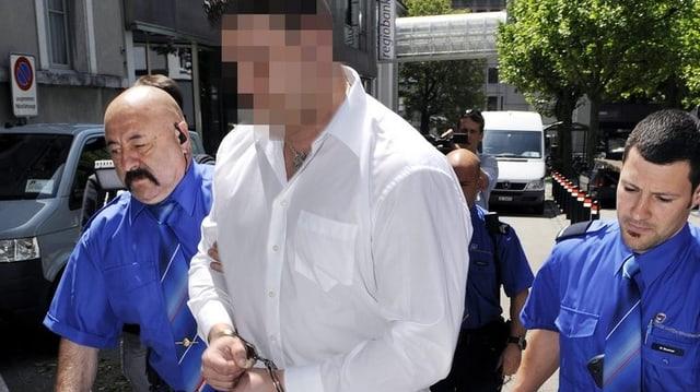 Zwei Polizisten führen einen Mann in Handschellen ins Gerichtsgebäude.