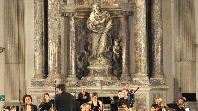 Eine Statue zwischen Säulen, darunter spielt ein Orchester.