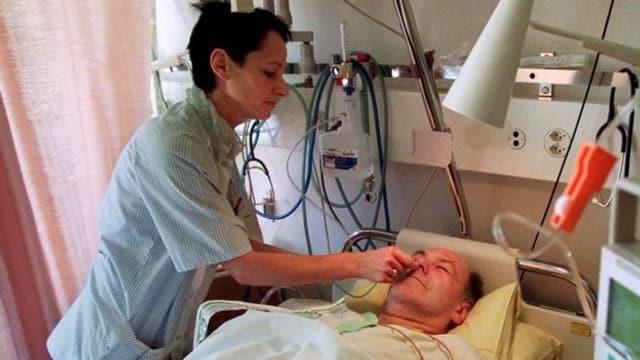 Eine Pflegefachfrau kümmert sich um einen Patienten