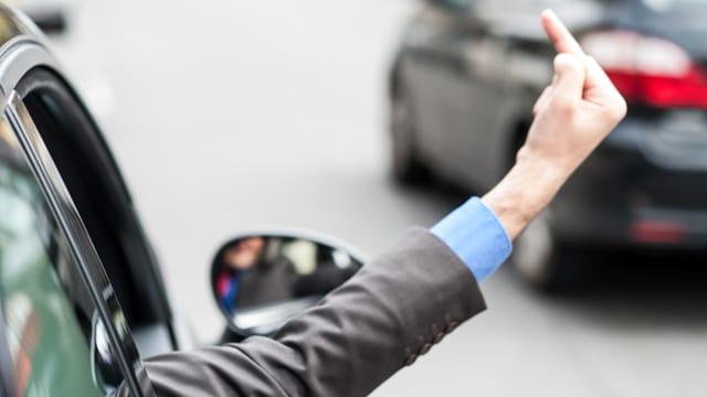 Autofahrer streckt Mittelfinger in die Luft