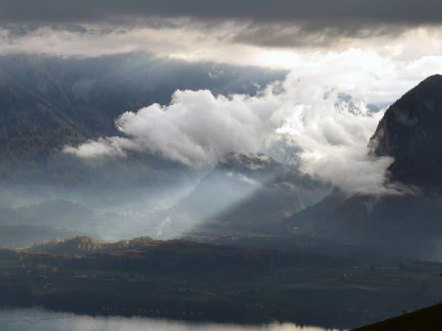 Blick von einem Berg ins Tal mit vielen Wolken.