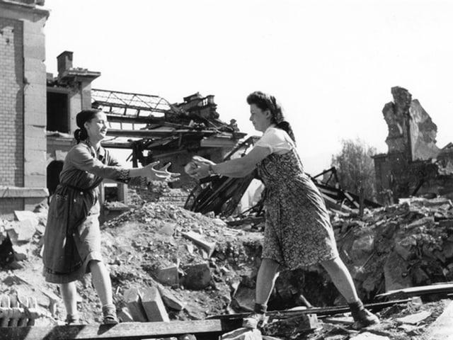 Zwei Frauen räumen Trümmer weg.