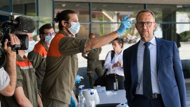 Regierungspräsident Norman Gobbi beim Fiebermessen durch einen Zivilschützer.