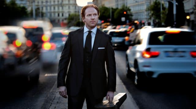 Ein Mann mit Anzug und Geigenkoffer auf einer Strasse.