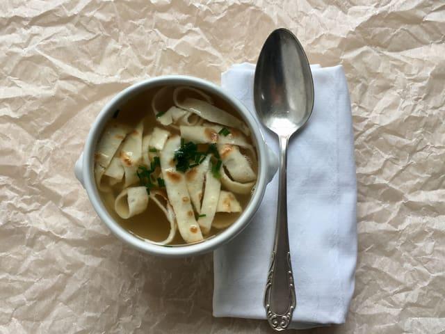 Eine Suppenschüssel mit Hühnerbouillon und Flädli. Daneben ein silberner Suppenlöffel.