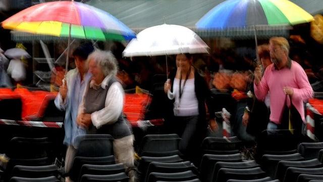 Menschen mit bunten Regenschirmen auf Tribüne.