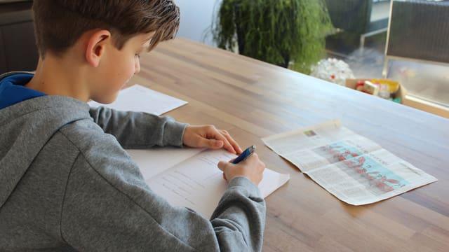 David schreibt auf einem Blatt Papier.
