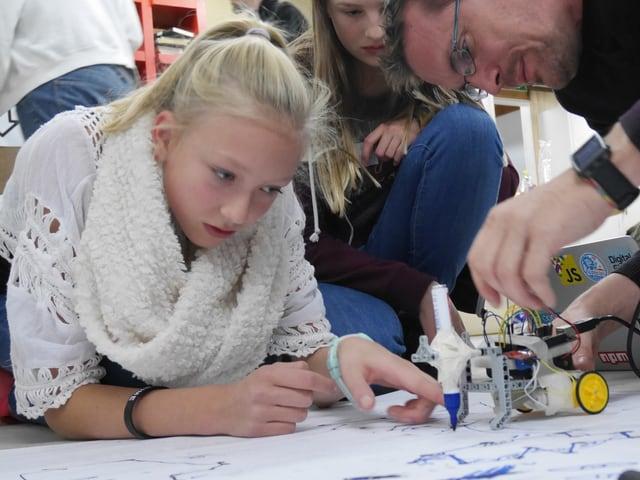 Zwei Mädchen und ein Mann sitzen auf dem Boden und schauen auf einen Lego-Roboter.