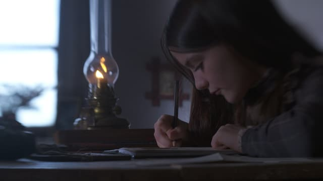 Ein Mädchen schreibt an ihrem Pult etwas in ein Tagebuch.