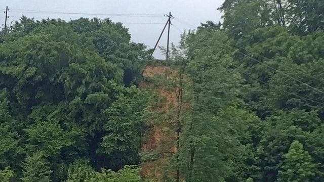 Erdrutsch an einem Hang, auf dem Grat steht noch ein Holz-Strommast.