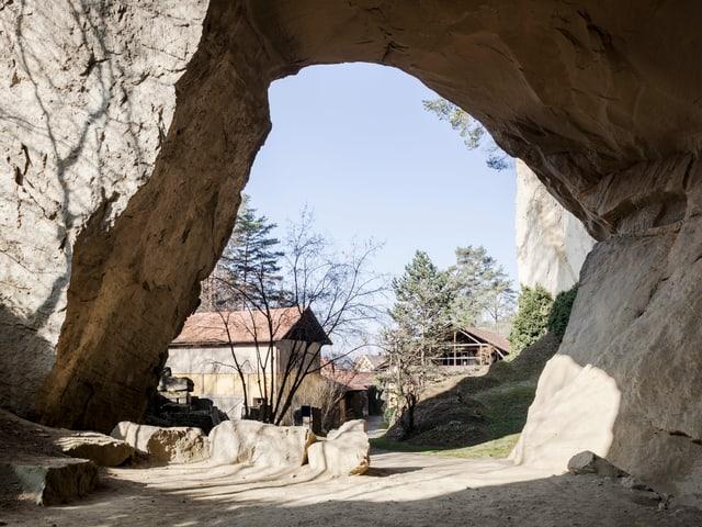 Blick aus einer hohen Grotte auf Häuser.