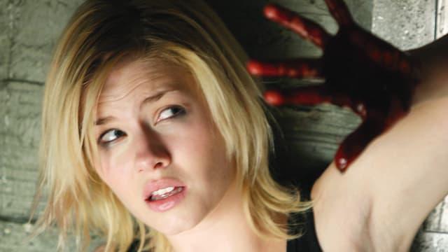 Eine blonde Frau mit blutverschmiertem Gesicht schützt ihren Kopf.