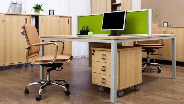 Blick in ein Büro mit leerem Tisch, zwei Stühlen und Büromöbeln.