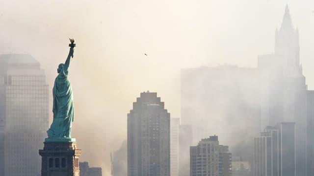Blick auf die Skyline von New York. Im Vordergrund ist die Freiheitsstatue zu sehen, die Gebäude dahinter sind in einer STaubwolke kaum zu sehen.