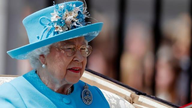 Nahaufnahme der Queen mit blauem Hut.