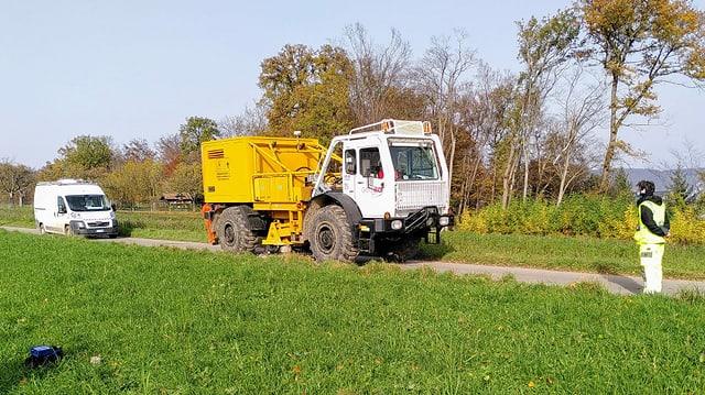 Weisses fahrzeug mit gelbem Aufbau auf schmalem Weg.