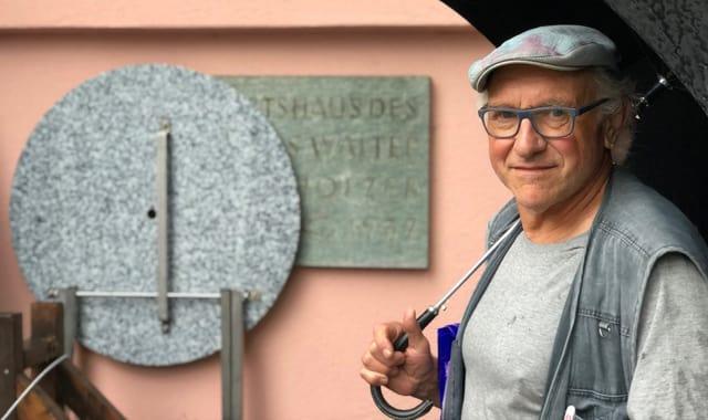 Wolfang Steiger steht vor der Mittelholzer-Gedenktafel an der Augustinergasse in St. Gallen.