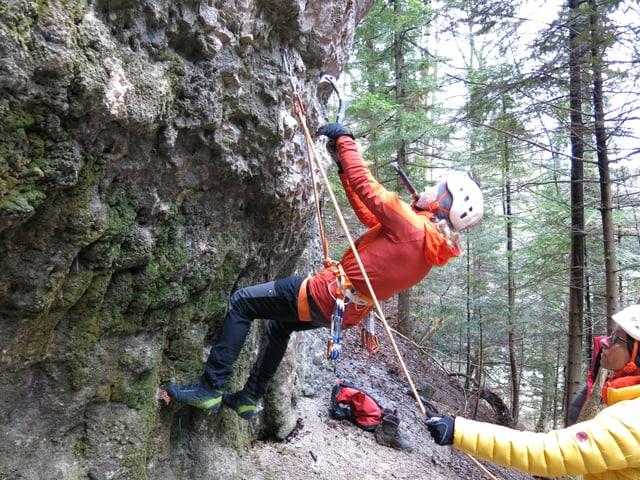 Kletterer an der Felswand, zweiter Kletterer sichert am Boden