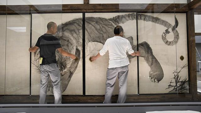Zwei Männer stellen Bild an die Wand