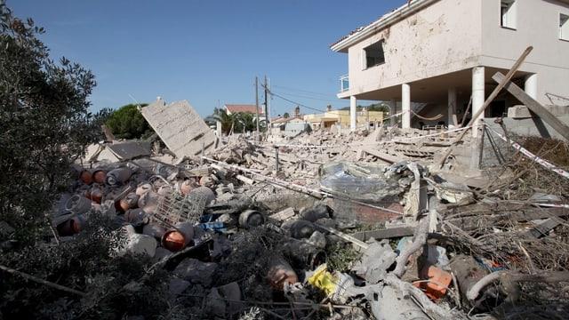 Zerstörten Haus. Im Vordergrund Trümmer, dazwischen Gasflaschen.