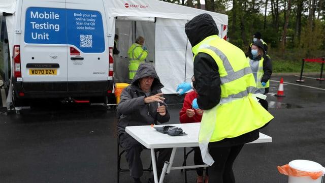 Angestellt des britischen Gesundheitswesen NHS an einer mobilen Test-Station.