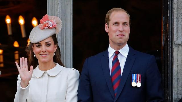 Herzogin Catherine und Prinz William winken von einem Balkon