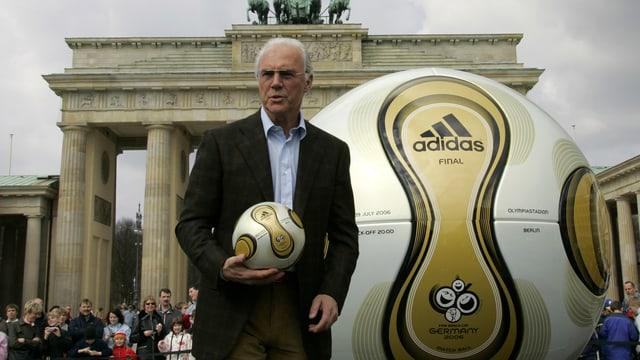 Beckenbauer mit einem Ball vor dem Brandenburger Tor.