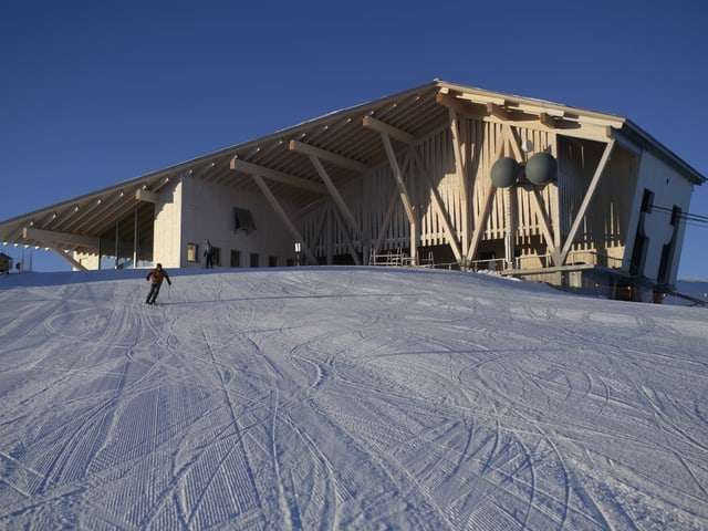 Ein Skifahrer wedelt vor der neuen Bergstation auf dem Chäserrugg die Piste hinab.