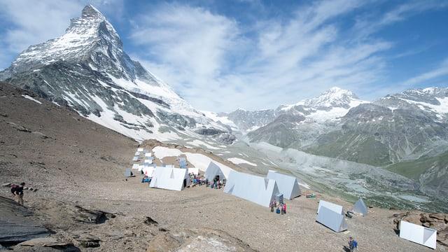 Zelte aus Holz und Aluminium stehen auf dem steinigen Boden, dahinter das Matterhorn
