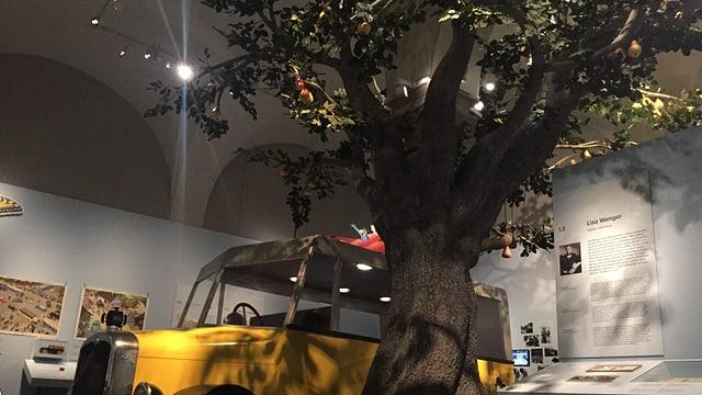 Ein grosser Baum und eine gelbes Postauto in einem Museum