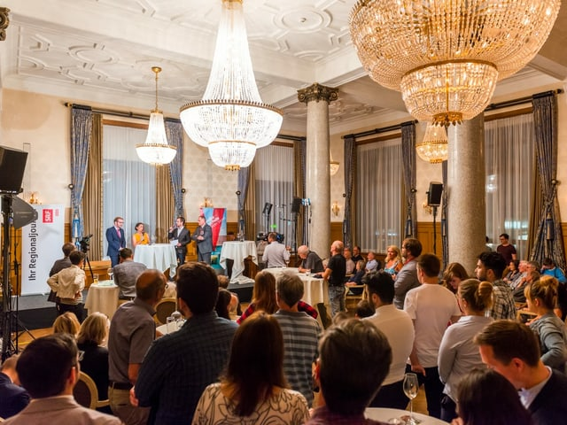 Saal mit vielen Zuschauerinnen und Zuscheuern und vorne ein kleines Pult, wo eine Diskussion stattfindet.