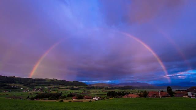 Regenbogen uns violetter Himmel.