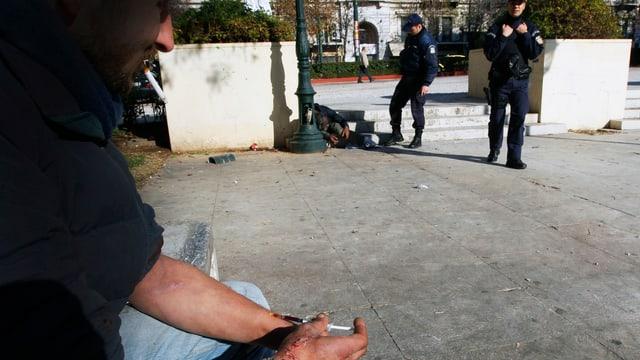 Polizisten beobachten zwei Männer.