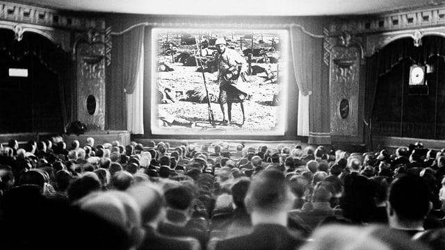 Blick auf ein Kinopublikum von hinten, das auf eine Kinoleinwand schaut. Dort ist ein Soldat zu sehen.