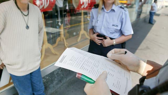 Ein Polizist der Stadtpolizei Zürich macht sich Notizen.