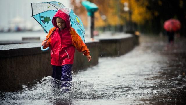 Ein Kind mit Schirm und wasserfesten Hosen, stapft durch das überflutete Ufer des Lago Maggiores