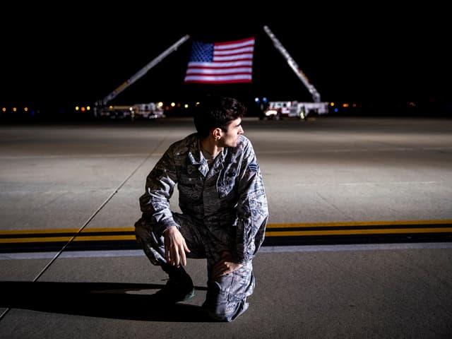 Ein Soldat vor einer grossen US-Flagge.