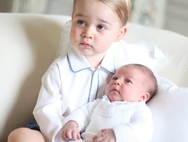 Prinz Geogre sitzend hält ein Baby (Prinzessin Charlotte) in der Hand. Beide sind weiss gekleidet.
