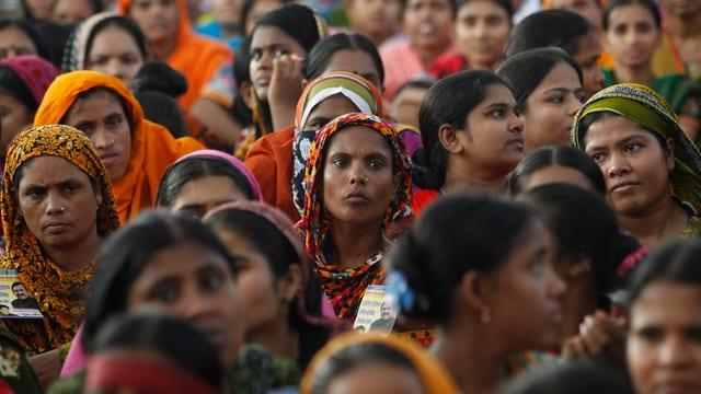 Frauen mit farbigen Kopftüchern hören sich aufmerksam eine Rede an.
