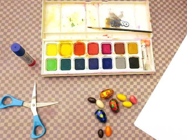 Du brauchst: Zwei Blätter Papier, Süssigkeiten, eine Schere, Leim und Wasserfarben