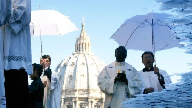 In einer Pfütze spiegelt sich die Spitze des Petersdoms.
